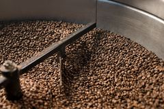 Coffee beans sifted and stirred in roasting machine Stock Photography