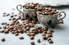 Coffee beans in silver vintage cups on wooden background. Close-up of coffee beans in silver vintage cups on wooden background, selective focus Royalty Free Stock Image