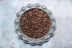 Coffee beans in silver vintage plate on wooden background. Close-up of coffee beans in silver vintage plate on wooden background Stock Photo
