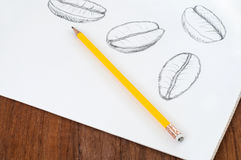 Coffee beans sketched on white with pencil. Artistic sketches of coffee beans on white paper with yellow pencil on wooden table Royalty Free Stock Photo