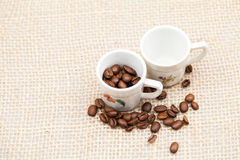 Coffee beans and small cups Royalty Free Stock Photos