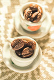 Coffee beans in a small lovely porcelain cups close-up. Stock Photos