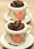 Coffee beans in a small lovely porcelain cups close-up. Royalty Free Stock Photos