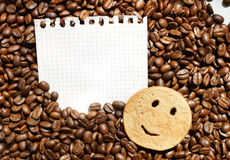 Coffee beans and smiling cookie on notebook sheet. Detached notepad graph paper sheet with smiling cookie on roasted coffee beans background Stock Photography