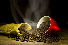 Coffee beans with smoke in coffee cup on brown background. Coffee beans with smoke in coffee cup on brown wood table background Stock Images
