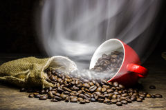 Coffee beans with smoke in coffee cup on brown background. Coffee beans with smoke in coffee cup on brown wood table background Royalty Free Stock Photo