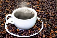 Coffee beans with smoke in coffee cup on brown Coffee beans back. Ground Stock Photography