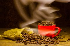Coffee beans with smoke in coffee cup on brown background.  Royalty Free Stock Photo