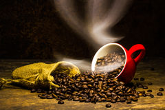 Coffee beans with smoke in coffee cup on brown background.  Royalty Free Stock Images