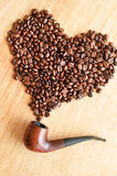 Coffee beans and smoking pipe Stock Image