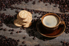 Coffee beans and some biscuits. A coffee cup and some biscuits with coffee beans on a wooden background Stock Photos