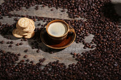 Coffee beans and some biscuits. A coffee cup and some biscuits with coffee beans on a wooden background Stock Image