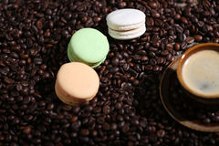 Coffee beans and some dessert. A coffee cup and some mcarons with coffee beans Royalty Free Stock Photography
