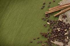 Coffee beans and some spices on green background. Coffee beans and spices on green background Stock Photo