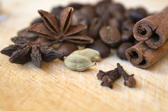 Coffee beans with spices. Anise, cinnamon sticks, cardamom and clove - on wooden cutting board, ingredients for aromatic coffee beverage Stock Photo