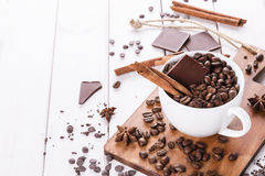 Coffee beans, spices and chocolate over white background Royalty Free Stock Photos