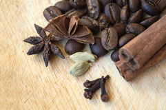 Coffee beans with spices on wooden surface Stock Images
