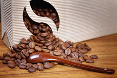 Coffee beans spill out of the box on the tabl Stock Images