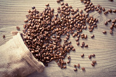 Coffee beans spill out of the sack Stock Image