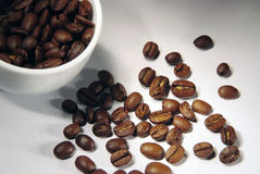 Coffee beans spilled from a cup. White cup and coffee beans Stock Photo