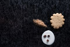 Coffee beans in spilled milk and brown sugar together with a cookie on a black background with silver lining. A sun shaped cookie biscuit glazed with sugar Stock Images