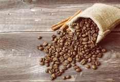 Coffee beans spilled out of the canvas sack. Vintage style photo of the coffee beans spilled out of the canvas sack at the wooden background Stock Photos