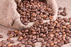 Coffee beans spilled out of the jute bag Stock Images