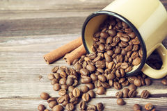Coffee beans spilled out of the old cup. Vintage style photo. Vintage style photo of the coffee beans spilled out of the old cup at the wooden background Royalty Free Stock Photography