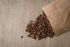 Coffee beans spilled out of a paper bag on a linen surface bag stock photos