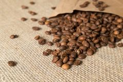 Coffee beans spilled out of a paper bag on a linen surface bag Royalty Free Stock Photo