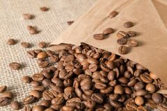Coffee beans spilled out of a paper bag on a linen surface bag stock images