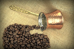 Coffee beans spilled from traditional Turkish copper coffee pot on a burlap Royalty Free Stock Photo