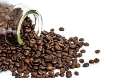 Coffee beans spilling bottle on white background. Coffee beans spilling out glass bottle on white background Stock Images