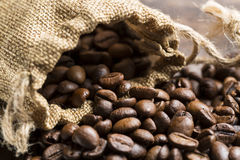 Coffee beans spilling from burlap sack Stock Images