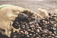 Coffee beans spilling from burlap sack on wooden background with smoke Stock Images