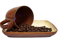 Coffee beans spilling from cup Stock Photo