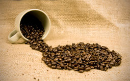 Coffee beans spilling from mug Stock Photography