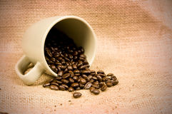 Coffee beans spilling from mug Stock Image