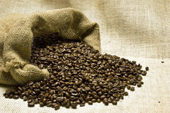 Coffee Beans Spilling Out On Burlap Background Royalty Free Stock Photos