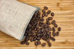 Coffee beans spilling out of burlap bag Royalty Free Stock Image