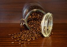 Coffee beans spilling out of a cristal jar Royalty Free Stock Photos