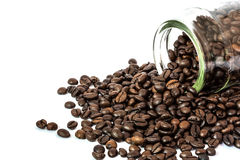 Coffee beans spilling out glass bottle Royalty Free Stock Photo