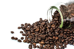 Coffee beans spilling out glass bottle Royalty Free Stock Image