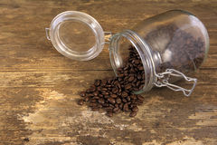 Coffee beans spilling out of a jar Stock Photography