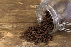 Coffee beans spilling out of a jar Stock Photo