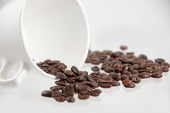 Coffee beans spilling out of a mug Royalty Free Stock Photos