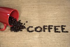 Coffee beans spilling out of red mug Royalty Free Stock Photos
