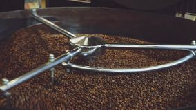 Coffee beans spinning in a frying machine, close up stock video footage