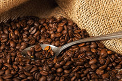 Coffee beans and spoon in a sack Stock Image
