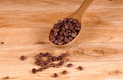 Coffee beans. Coffee spoon on wooden background Royalty Free Stock Photos